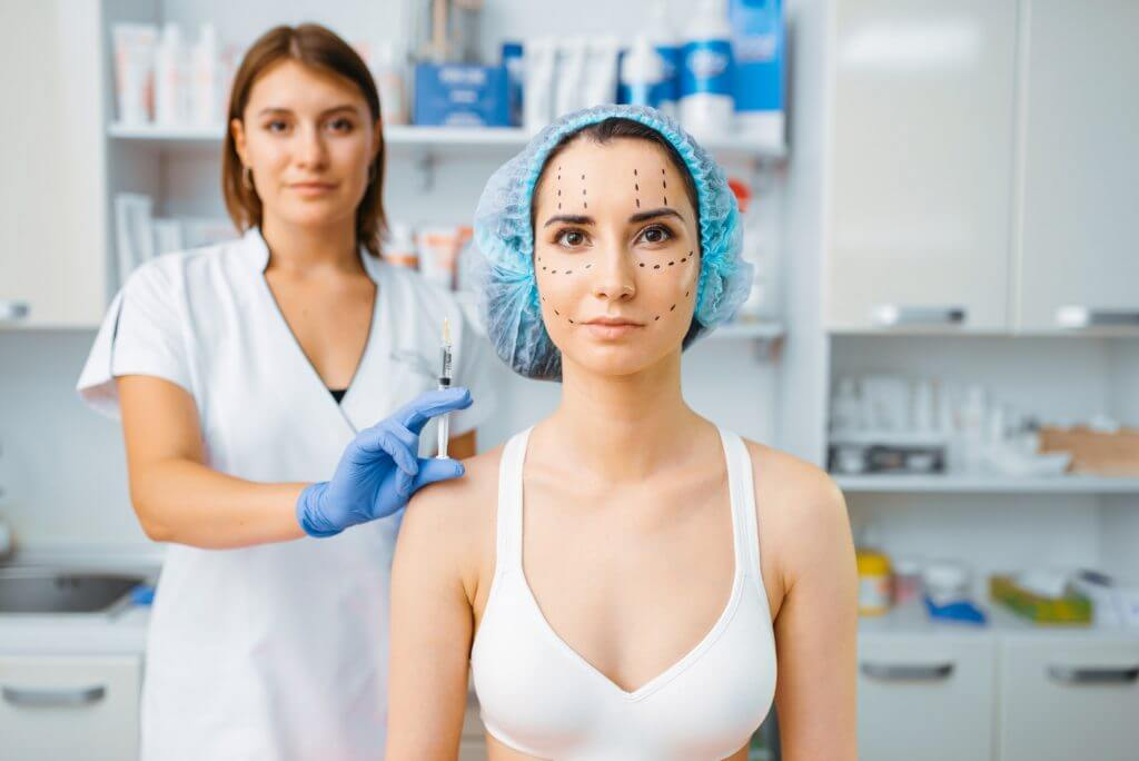 Cosmetician holds botox syringe and female patient