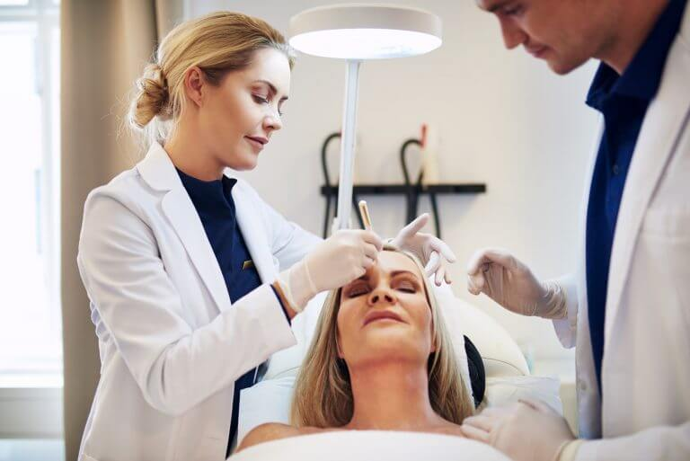 Woman lying on clinic table with doctors discussing surgery options